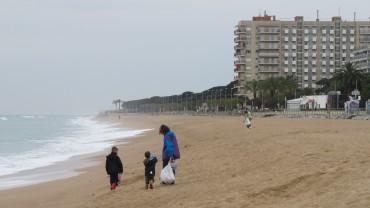 Voluntaris en família rastrejant la platja